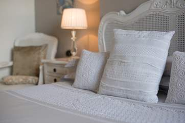 Pretty lace cushions complement the linens.