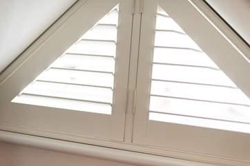 Shutters dress the triangular window in Bedroom 2.