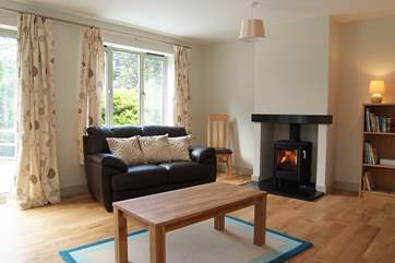 The open plan living-room is very spacious, with a wood-burner in the sitting-area.