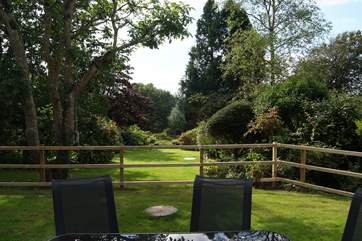 The view across the lovely garden is enhanced by mature shrubs and trees which offer seclusion and tranquility.