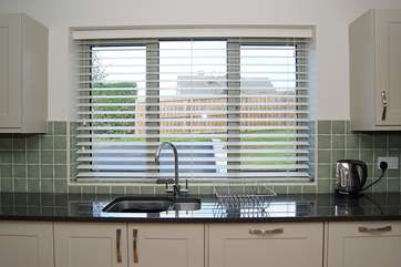 The kitchen looks out over the front garden and parking-area, all securely enclosed.