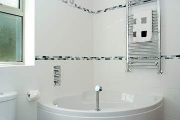 The ground floor en suite bathroom has a corner bath as well as the walk-in shower.
