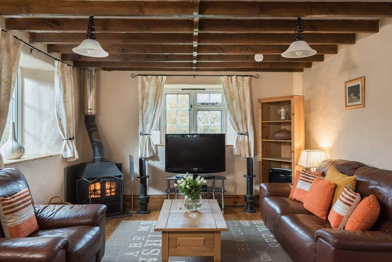 The sitting-area features a surround sound television and a welcoming wood-burner.
