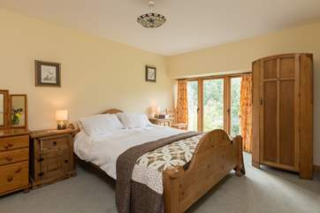 Back inside, this is the master bedroom on the first floor.  Floor to ceiling windows give you wonderful views from your bed