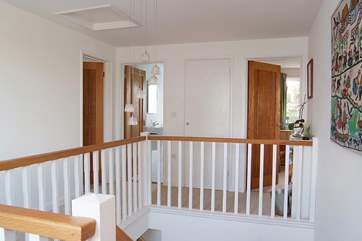 The wide, light landing at the top of the stairs looks down over the spacious entrance hall.
