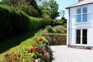 The garden is bordered by beautifully planted colourful flowerbeds.