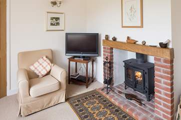 The sitting room has comfortable sofas and looks out over the garden and open countryside.