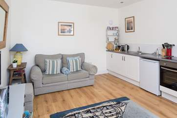 The open plan design of this cottage has plenty of comfortable space, the kitchen area is cleverly fitted along one wall.
