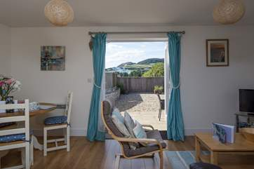 The cheerful open plan living area opens onto the sunny patio, with wonderful views of Golden Cap.