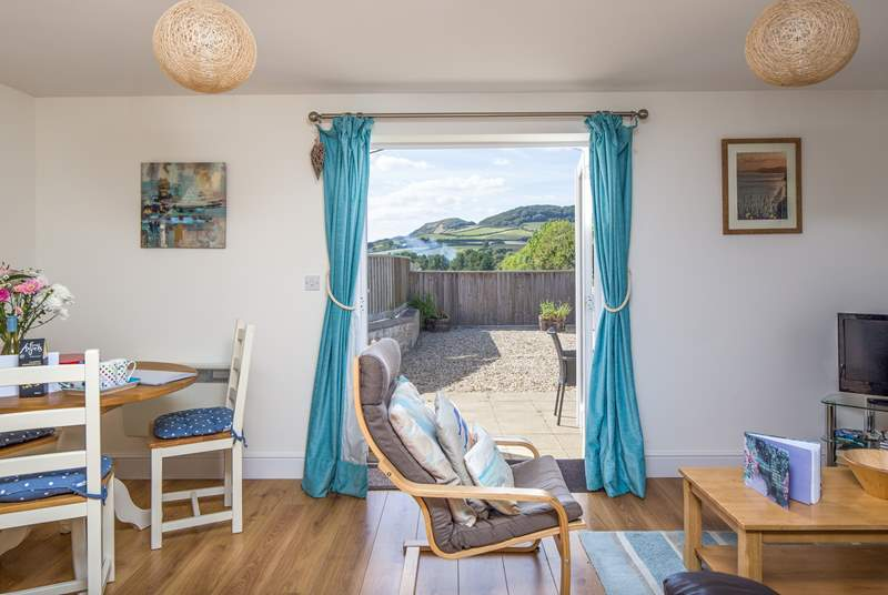 The cheerful open plan living area opens onto the sunny patio, with wonderful views of Golden Cap
