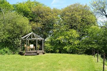 The garden and the pergola with its outdoor furniture.