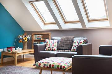 Velux windows on both sides of the open-plan living-room allow light to flood in.
