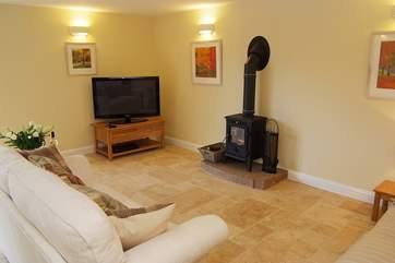Comfortable sofas surround the wood-burner.