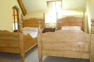 Bedroom1 is light and airy with these delightful wooden twin beds.