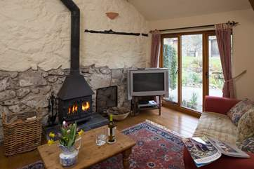 The comfortable sitting-room has a cosy wood-burner.