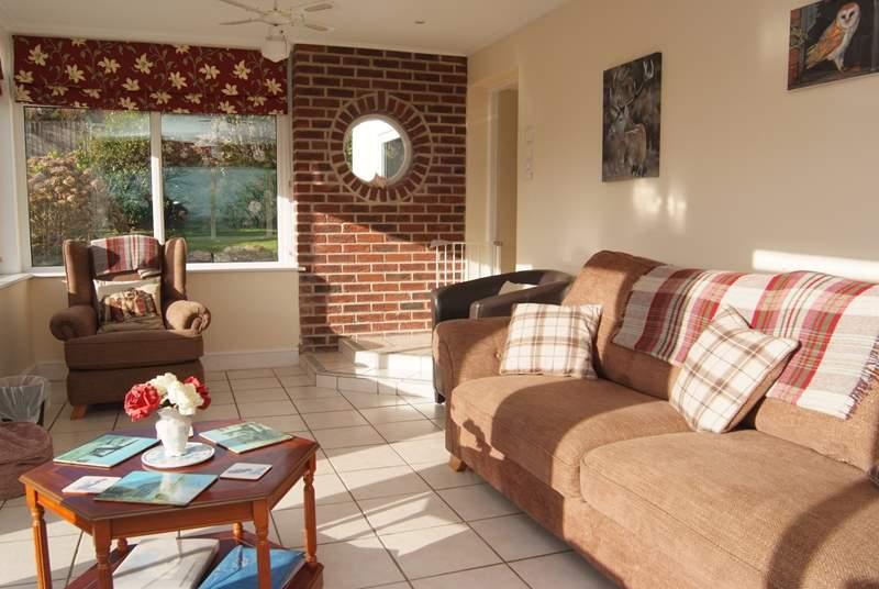 The comfortable sitting-room overlooks the garden.