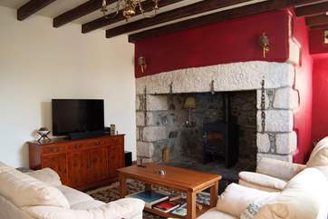 The second sitting-room includes a wood-burner in the huge original stone fireplace.