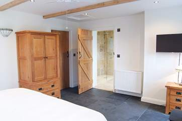 The room is furnished with solid wood wardrobe and side tables.