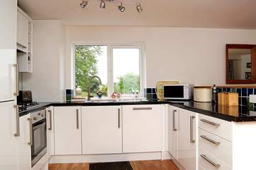 The white high-gloss kitchen is very well-equipped....
