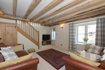 The sitting room overlooks the courtyard and the stairs lead straight up into one of the spacious double bedrooms.