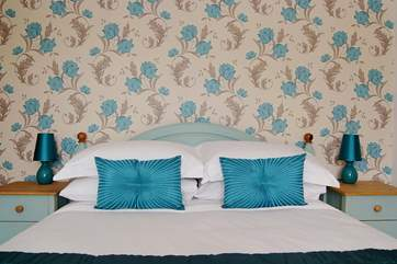 Crisp white hotel-quality bed linens complement the hand-painted bed and bedside cabinets.