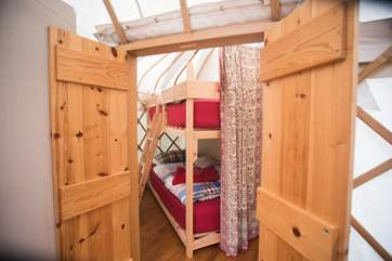 Double doors lead into the attached yurt which houses the bunk beds and the shower-area.