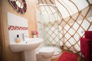 The en suite shower-area in the baby yurt has a proper hot water shower cubicle, a flushing WC and wash-basin.