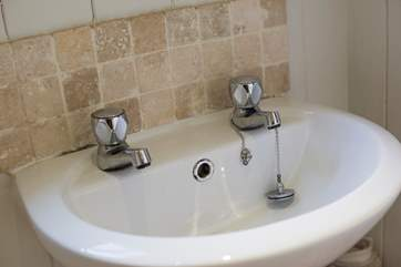 There is a wash-basin with hot and cold running water.