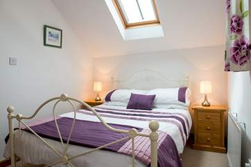 Both bedrooms have bright linens and lovely bedsteads.