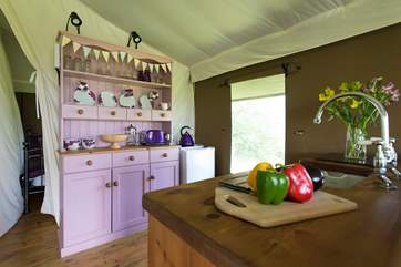 The pink dresser is home to all your crockery and cutlery and is next to the full size fridge.