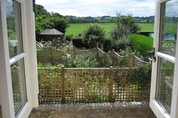The cottage is in an edge of village setting and this is the view from one of the upstairs windows - overlooking the Owner's beautiful gardens and to the countryside beyond.