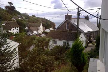 The view from the bedroom across cottage rooftops to the sea.