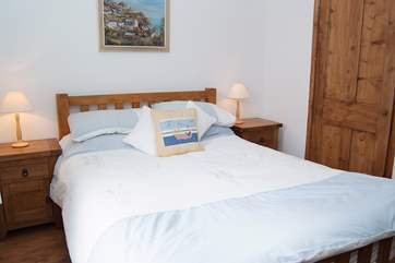 The bedroom is a comfortable haven with both modern and antique wood furniture.