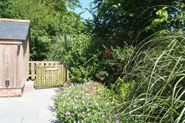 The pretty patio garden is surrounded by shrubs with the gate open onto the coast path.