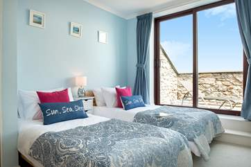 The delightful twin bedroom with a sliding door leading out to the balcony.