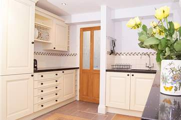There is a really good-sized kitchen with lovely painted units, a utility-area and shower-room beyond.