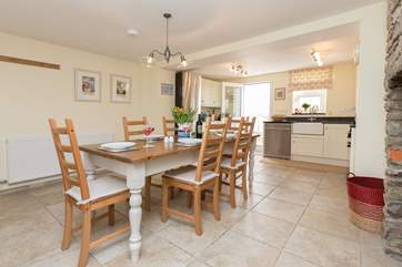 You step into this lovely kitchen with its welcoming farmhouse kitchen table, the door at the far end also opens to the courtyard patio