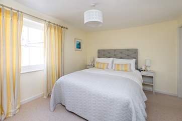 The master bedroom is beautifully designed with calm colours and a very comfortable bed. The en suite shower-room is to the right of the room.
