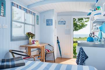 The king-size bed is positioned to look straight out the stable door to the sea in the distance.