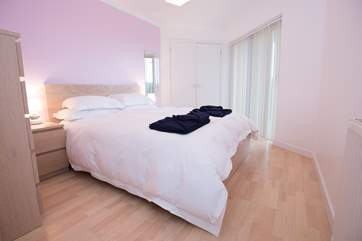 The ground floor en suite master bedroom has doors out to the decked terrace.