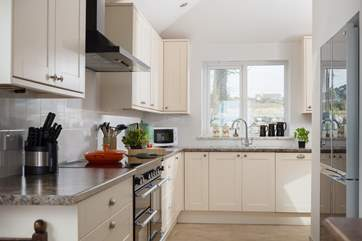 A modern and well-equipped kitchen including a range cooker and a large fridge/freezer.