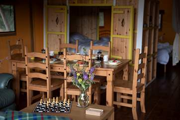 Dining table with the comfortable cabin bed in the background.