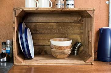 Rustic wooden bowls and enamel crockery complement the glamping theme.