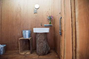 The very interesting cloakroom with its wash-basin on a tree trunk!