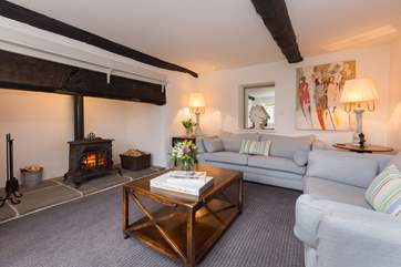 There is a fabulous sitting room with a perfect balance of original farmhouse character and luxurious contemporary living