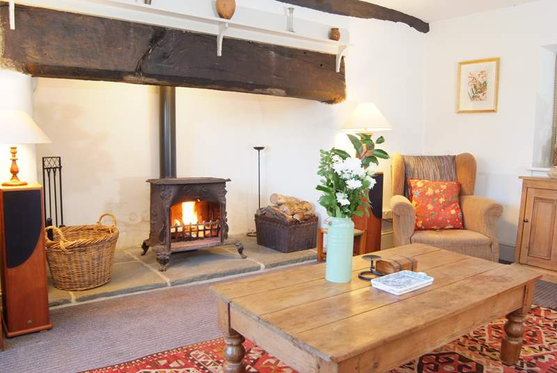 The living room has a huge fireplace with a vintage French wood burning stove.