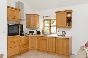 The kitchen is fitted around the corner of the open plan living space.