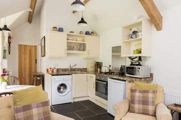 There is a kitchen tucked into one corner of the open plan living space, well-equipped with all you could need for your stay.