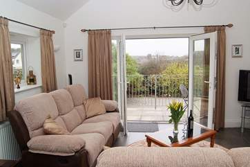 French doors open onto the balcony bringing the outside in and making the most of the wonderful views.