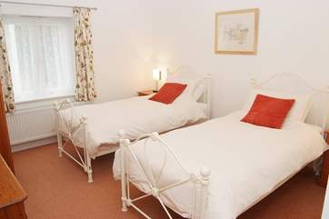 The comfortable twin-room is tastefully furnished with ornate beds and pine furniture.